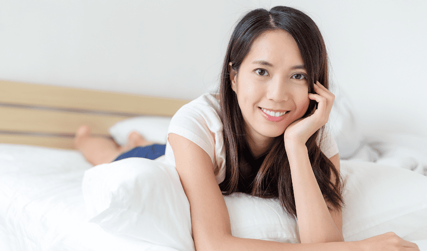 Lady laying on bed doing pelvic floor exercise